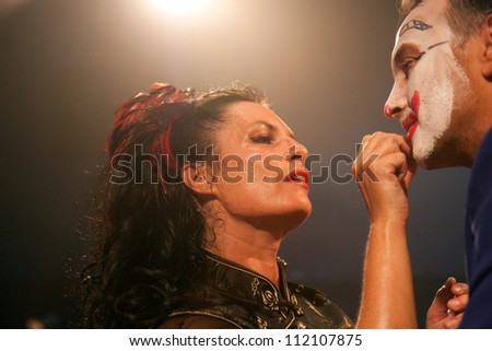 AURILLAC, FRANCE - AUGUST 22: a woman puts make-up on the face of a clown as part of the Aurillac International Street Theater Festival,show by the Company Off ,on august 22, 2012, in Aurillac,France. - stock photo