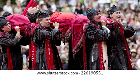 AURILLAC, FRANCE-AUGUST 22: actors carry Lenin body for his funeral as part of the Aurillac International Street Theater Festival, cie teatro del silencio there august 22, 2014 in Aurillac, France. - stock photo