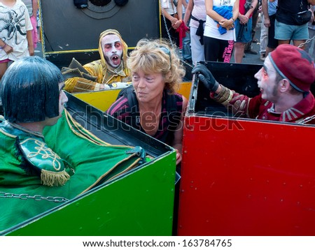 AURILLAC, FRANCE - AUGUST 23: Actors, moving in colored boxes, have surrounded a poor spectator, as part of the Aurillac International Street Theater Festival, on august 23,2013, in Aurillac,France.  - stock photo
