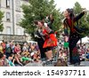 AURILLAC, FRANCE - AUGUST 23: actors perched on bar stools in the middle of the crowd,as part of the Aurillac International Street Theater Festival, Cie Oposito,on august 23, 2013, in Aurillac,France  - stock photo