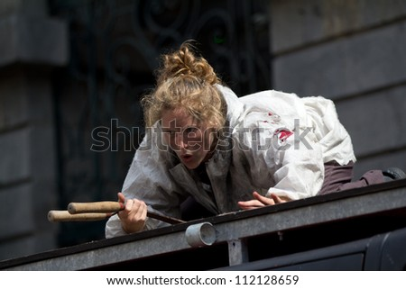 AURILLAC, FRANCE - AUGUST 22: actress holding a pair of secateurs on the roof of a car as part of the Aurillac International Street Theater Festival, Company O ,on august 22, 2012, in Aurillac,France. - stock photo