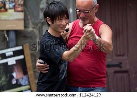 AURILLAC, FRANCE - AUGUST 24: an actor dances with a spectator in the street as part of the Aurillac International Street Theater Festival, show Robot Nozomi, on august 24, 2012, in Aurillac,France. - stock photo
