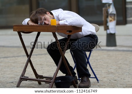 AURILLAC, FRANCE - AUGUST 24: an actor is lying on a table as part of the Aurillac International Street Theater Festival, show by the Schizophr�¨nes associ�©s, on august 24, 2012, in Aurillac,France. - stock photo