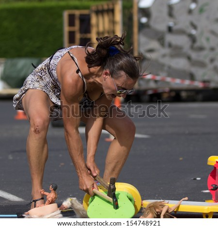 AURILLAC, FRANCE - AUGUST 22: an actress breaks toys with a hammer as part of the Aurillac International Street Theater Festival, Company Monsieur Linea,on august 22, 2013, in Aurillac,France  - stock photo