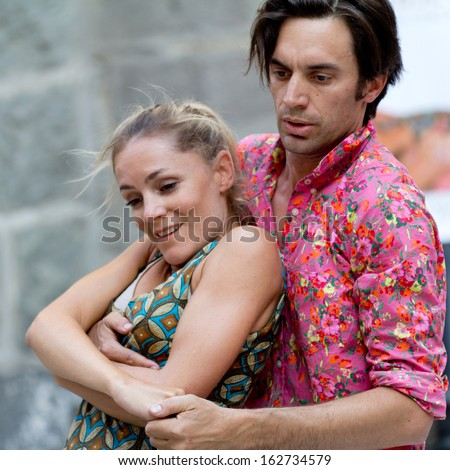 AURILLAC, FRANCE - AUGUST 23: An embracing couple of artists dances tango, as part of the Aurillac International Street Theater Festival, cie Moebius, on august 23, 2013, in Aurillac,France  - stock photo