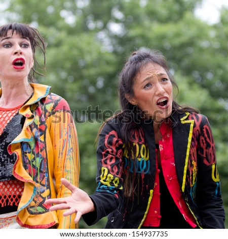 AURILLAC, FRANCE - AUGUST 23:  an expressive actress wears a colored costume as part of the Aurillac International Street Theater Festival, Cie Oposito,on august 23, 2013, in Aurillac,France  - stock photo