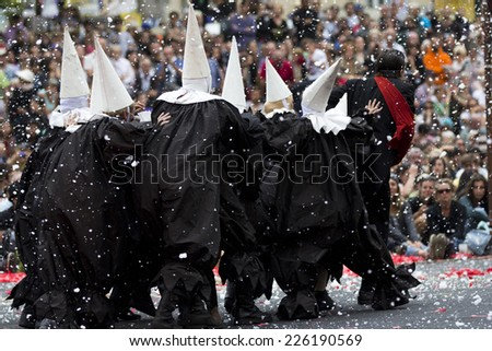 AURILLAC, FRANCE-AUGUST 22: disguised people walk under the snow as part of the Aurillac International Street Theater Festival, cie teatro del silencio there august 22, 2014 in Aurillac, France. - stock photo