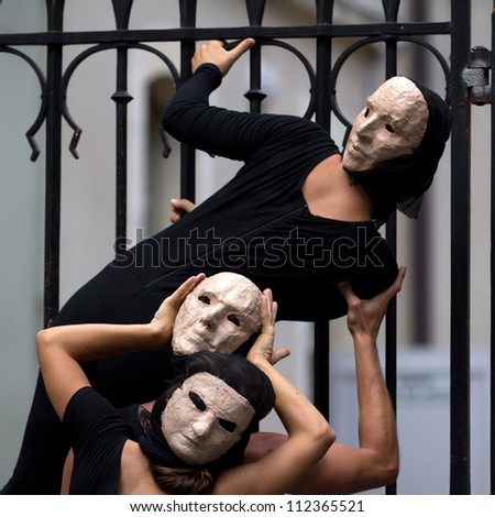 AURILLAC, FRANCE - AUGUST 23: enigmatic and worrying actors wearing a white mask, Aurillac International Street Theater Festival, show La diagonale du Fou, on august 23, 2012, in Aurillac,France. - stock photo