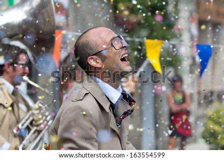AURILLAC, FRANCE - AUGUST 23: hail of confetti on an actor, as part of the Aurillac International Street Theater Festival, cie Rhinofanpharyngite,on august 23, 2013, in Aurillac,France  - stock photo