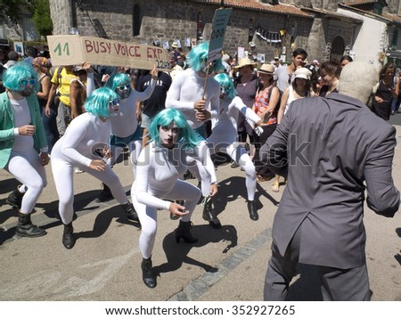 AURILLAC, FRANCE - AUGUST 19: parade of street performers wearing green-blue wigs and white uniforms, as part of the Aurillac International Street Festival, on august 19, 2015, in Aurillac, France.