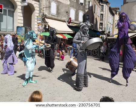 AURILLAC, FRANCE, AUGUST 21: Some costumed artists walk on stilts in the street. They play music as part of the Aurillac international Street Theater Festival, on august 21, 2014 in Aurillac, France. - stock photo