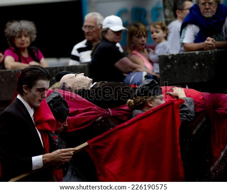 AURILLAC, FRANCE-AUGUST 22: spectators look at the Lenin funeral as part of the Aurillac International Street Theater Festival, cie teatro del silencio there august 22, 2014 in Aurillac, France. - stock photo