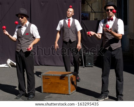 AURILLAC, FRANCE - AUGUST 22: Three jugglers playing with some red balls  as part of the Aurillac International Street Theater Festival, Cie Kiblos,on august 22, 2013, in Aurillac,France  - stock photo