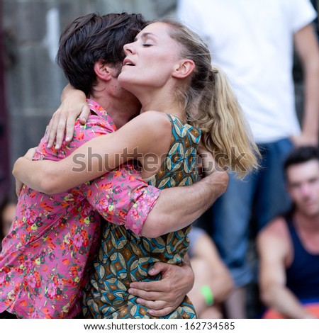 AURILLAC, FRANCE - AUGUST 23:Two embracing dancers, as part of the Aurillac International Street Theater Festival,cie Moebius, on august 23, 2013, in Aurillac,France  - stock photo