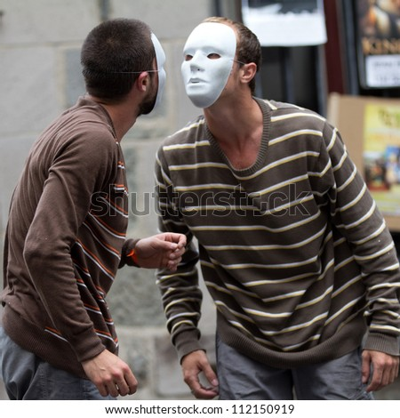 AURILLAC, FRANCE - AUGUST 24: two masked dancers, face to face, as part of the Aurillac International Street Theater Festival,show by the Company Idem,on august 24, 2012, in Aurillac,France. - stock photo