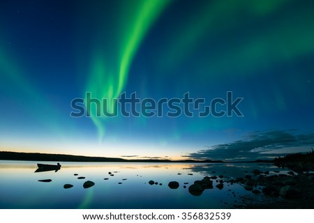 Aurora at Dusk - Bands of curvy aurora borealis appear over a northern rocky lake right after sunset. - stock photo