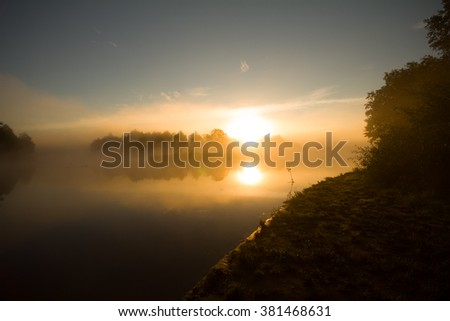 Aurora. Beautiful sunrise over misty river, end of summer - stock photo