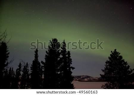 Aurora Borealis display and lots of stars in clear night sky, image taken at the shore of Lake Laberge, Yukon Territory, Canada - stock photo