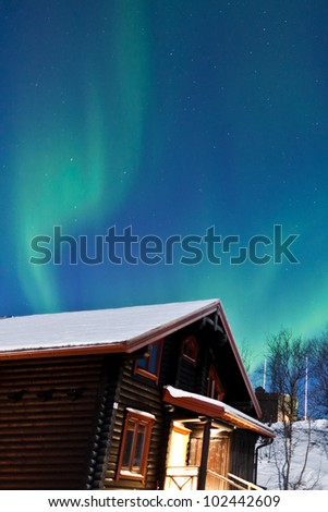 Aurora Borealis in Norway above a cabin - stock photo