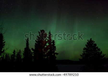 Aurora Borealis (Northern lights) display and lots of stars in clear night sky, image taken at the shore of Lake Laberge, Yukon Territory, Canada - stock photo
