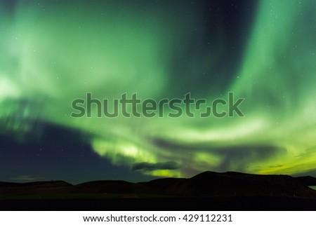 Aurora borealis. Northern lights in Iceland Myvatn. Stars in night sky illuminated by northern lights - stock photo