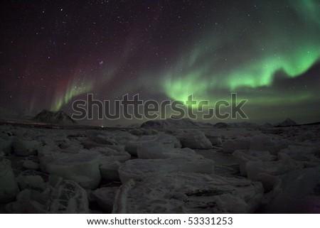 Aurora Borealis over the frozen fjord - stock photo