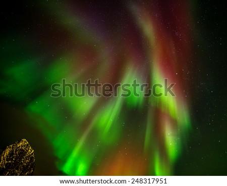 Aurora borealis (Polar lights) over Lilandstinden peak and Hamnoy village in the North of Europe (fragment) - Reine, Lofoten islands, Norway - stock photo
