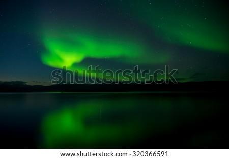 Aurora lights dancing over calm lake in Abisko (Aurora borealis) - stock photo
