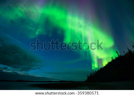 Aurora on Lake - Bright cloud-shape aurora borealis beam down over a lake from the starry night sky.  - stock photo
