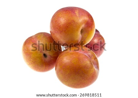 Aurora plums (prunus domestica) are a stone fruit with a groove running down on one side. They are sweet in taste and have yellow flesh.  - stock photo
