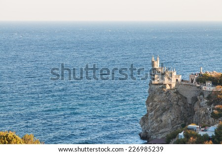 Aurora rock with Swallow's Nest castle on Southern Coast of Crimea in evening - stock photo