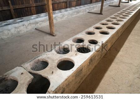 Auschwitz Birkenau a former Nazi extermination camp in Brzezinka, Poland near Oswiecim. Horrible toilets latrines in one of the buildings. - stock photo
