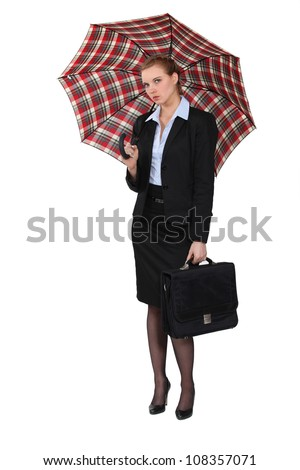 Austere businesswoman holding a briefcase and an umbrella - stock photo
