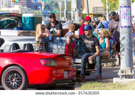 AUSTIN, TEXAS: APRIL 6 2013: Spectators relaxing in the sun during a car rally on South Congress Avenue in Austin Texas - stock photo