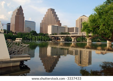 Austin, Texas downtown skyline, embraced by the beauty of nature. Austin downtown is next to the colorado river's infamous Town Lake paddle boat in foreground - stock photo