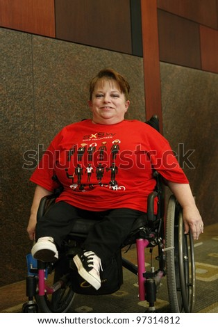AUSTIN, TEXAS - MAR 9: SXSW 2012 South by Southwest 2012 Annual music, film, and interactive conference and festival on March 9, 2012 in Austin, Texas. Festival is held from March 9-18.   Wheelchair bound person in SXSW t-shirt attending the conference - stock photo