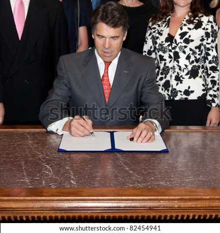 AUSTIN, TX - AUGUST 20: Texas Governor Rick Perry signs legislation on August 20, 2009, in the Texas State Capitol Building in Austin. - stock photo