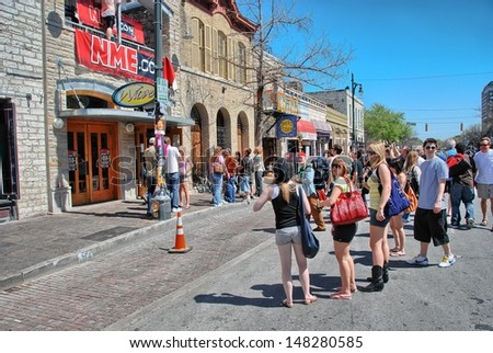 AUSTIN, TX - MAR 14: Tourists enjoy SXSW festival in city streets, March 14 2008 in Austin. SXSW began in 1987, and has continued to grow in size every year. - stock photo