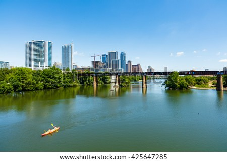 Austin, TX USA - April 14: Skyline view of the downtown area along the Colorado River with kayakers cruising by.