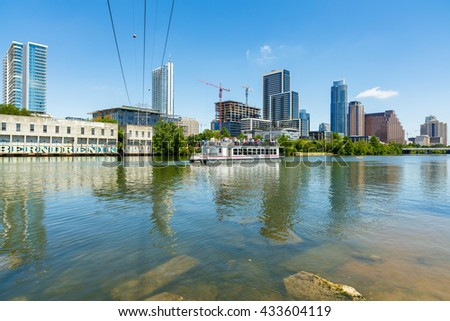 Austin, TX USA - April 14, 2016: Skyline view of  the downtown district along the Colorado River with a tour boat cruising by.