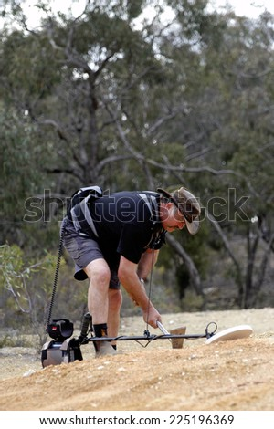 AUSTRALIA - APRIL 24: Gold miner at work detecting gold nuggets with a metal detector, April 24, 2007 - stock photo