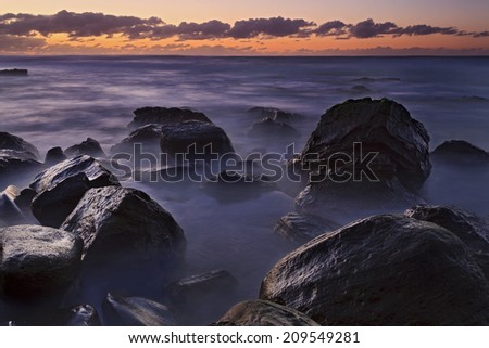 Australia beach rocks wet of surfing waves at sunrise NSW National park