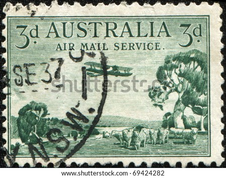 AUSTRALIA - CIRCA 1937: a stamp printed in Australia shows plane over a pasture with sheep, circa 1937 - stock photo