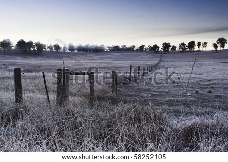 australia country farm winter cold weather frost on grass and land, agriculture site with fence border - stock photo