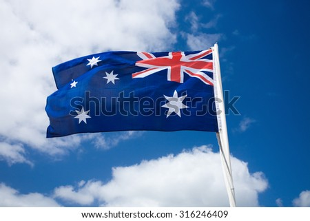 Australia flag waving in the wind against blue sky