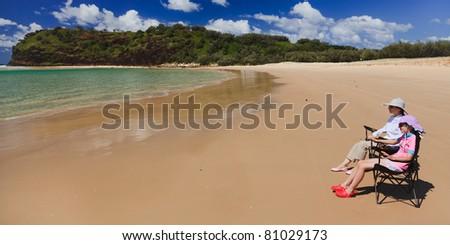 australia fraser island beach couple in chair under summer sun blue sky and nice ocean water - stock photo