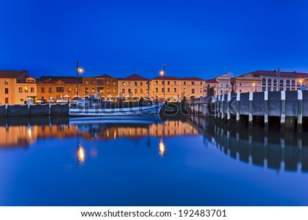 Australia Hobart city historic houses at water edge at sunset illuminated with reflection in still harbour water and fishing boat at jetty - stock photo