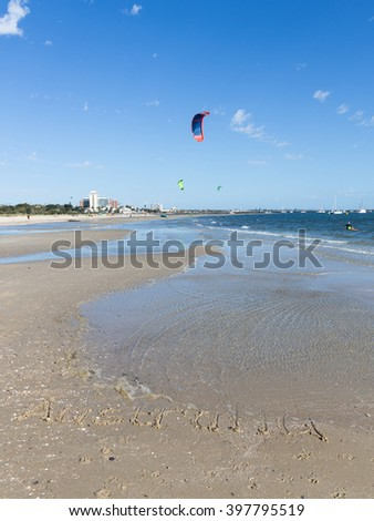 Australia inscription on the sand with shells on a large beautiful Australian beach, and unrecognizable people go kite surfing, and beautiful bright sails flying over blue sea, Australia - stock photo
