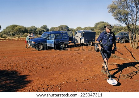 AUSTRALIA - MAY 5: A group of gold miners parked on an Australian track to the point on the map while another seeks a nugget of gold lost in the sector, may 5, 2007.