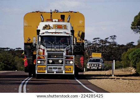 AUSTRALIA - MAY 20: Pilot car following a huge Australian truck to close the convoy while another above the truck on an Australian road, may 20, 2007. - stock photo